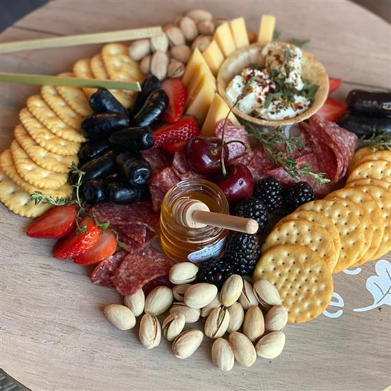 charcuterie board with assorted fruits, crackers and nuts