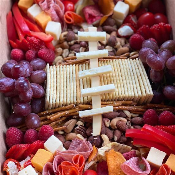 charcuterie board with assorted meats, cheeses, fruits, vegetables and nuts
