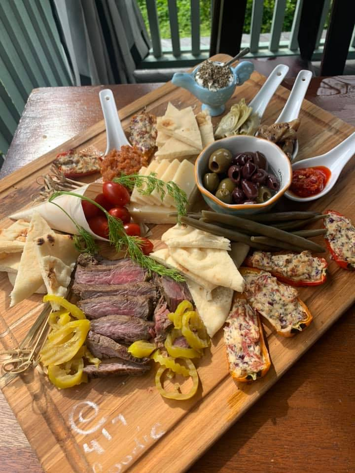 charcuterie board with assorted meats, cheeses, fruits, vegetables, crackers and nuts