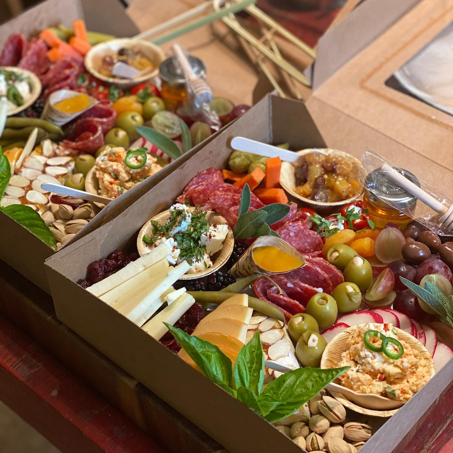 two charcuterie boards with assorted meats, cheeses, fruits, vegetables, crackers and nuts in boxes