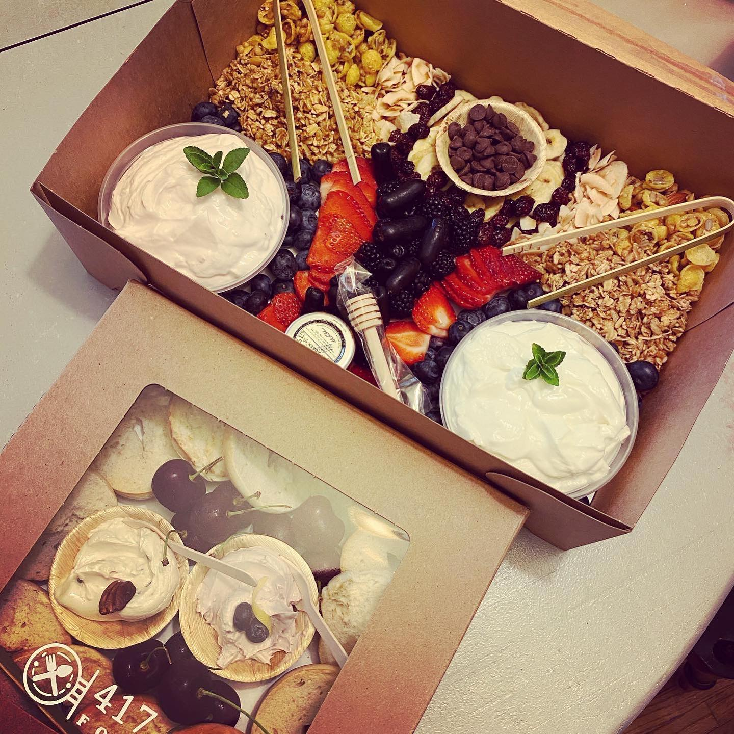 yogurt board with granola, assorted fruits and nuts in a box