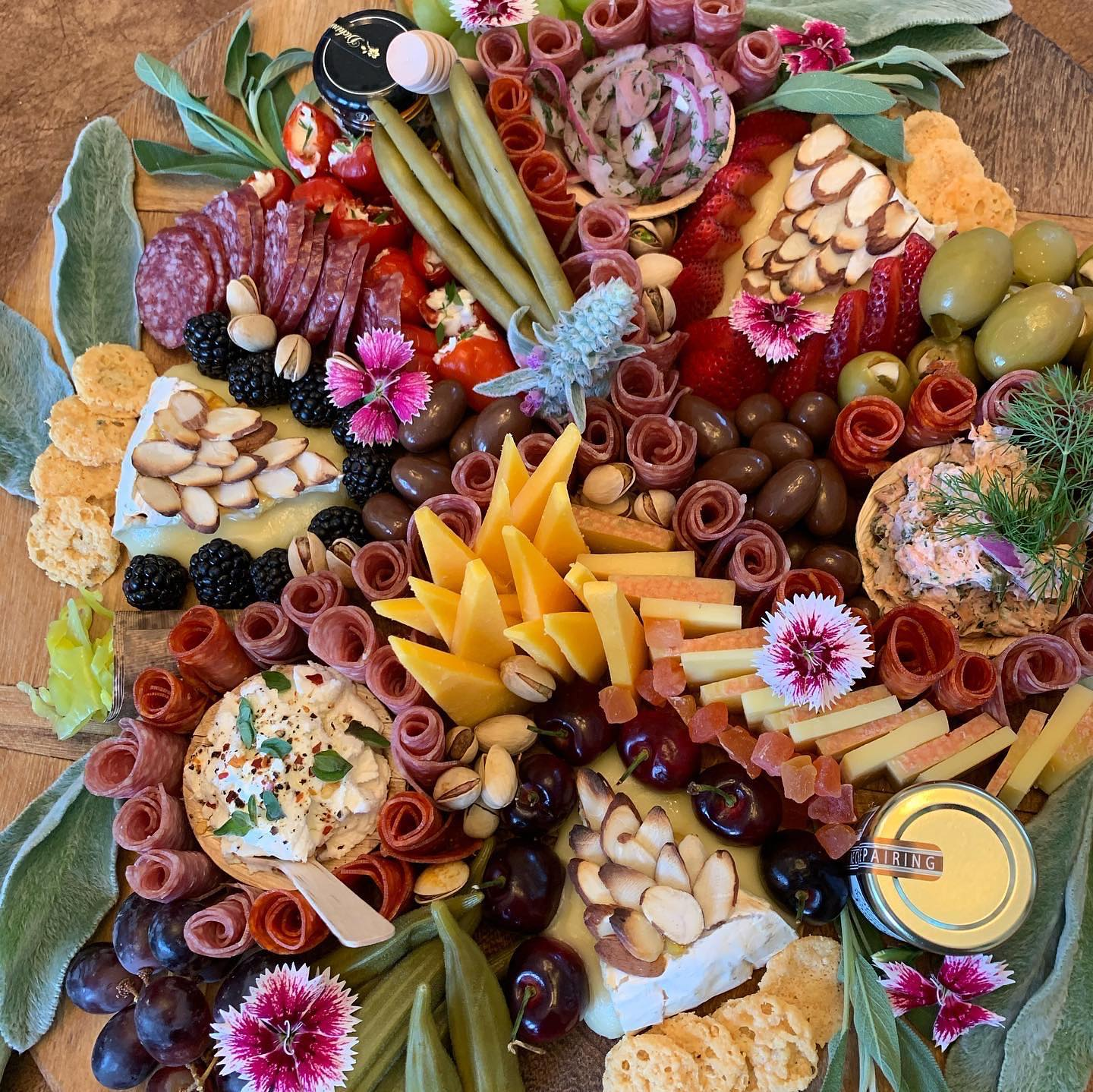 charcuterie board with assorted meats, cheeses, fruits, vegetables, crackers, jams and nuts
