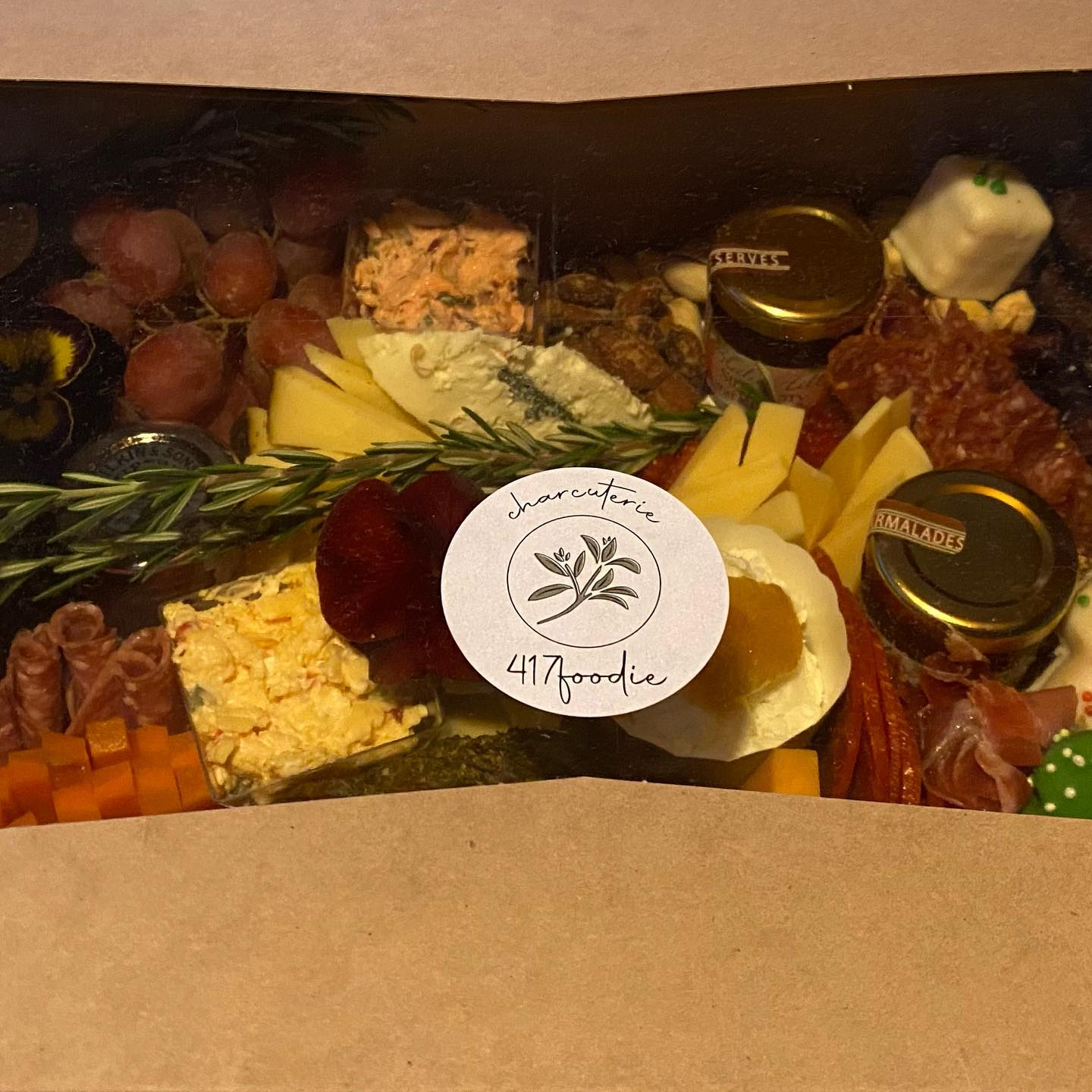 charcuterie board with assorted meats, cheeses, fruits, vegetables and nuts in a box
