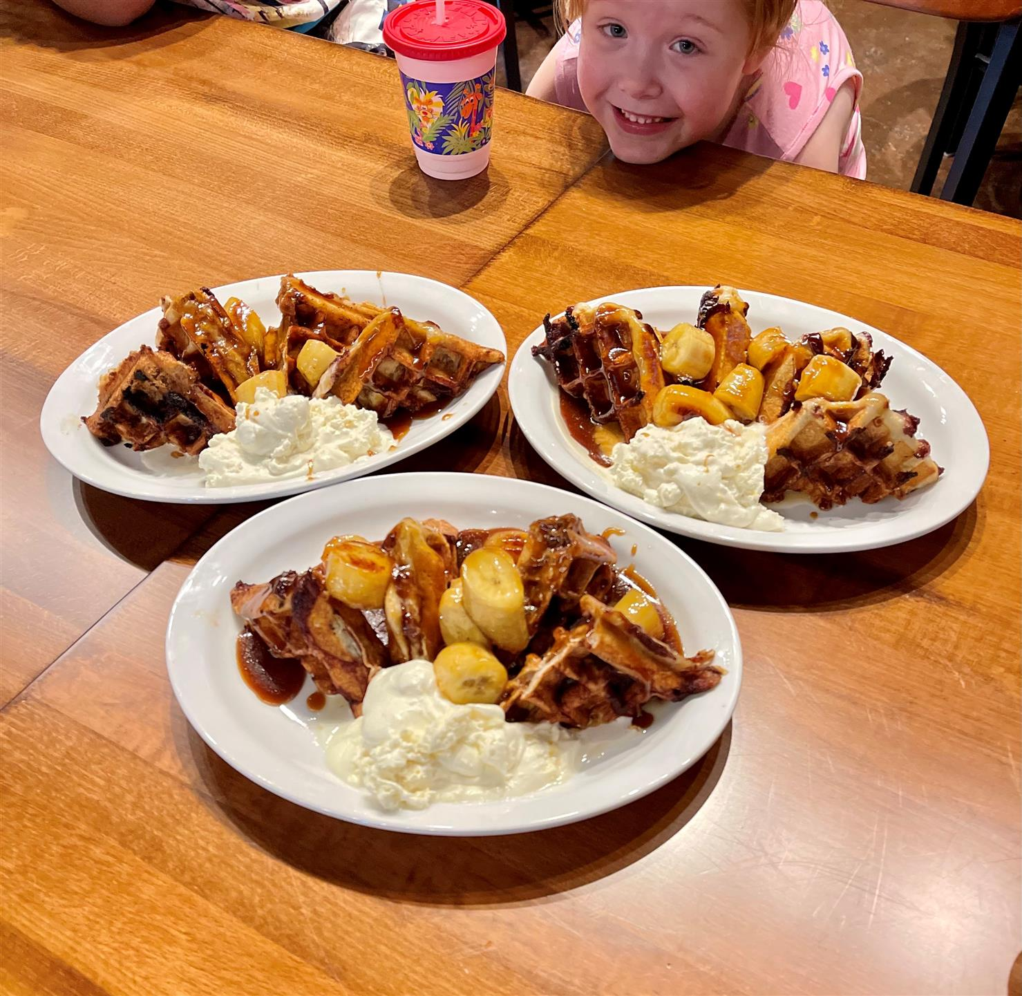 three plates of waffles with bananas and a little girl smiling