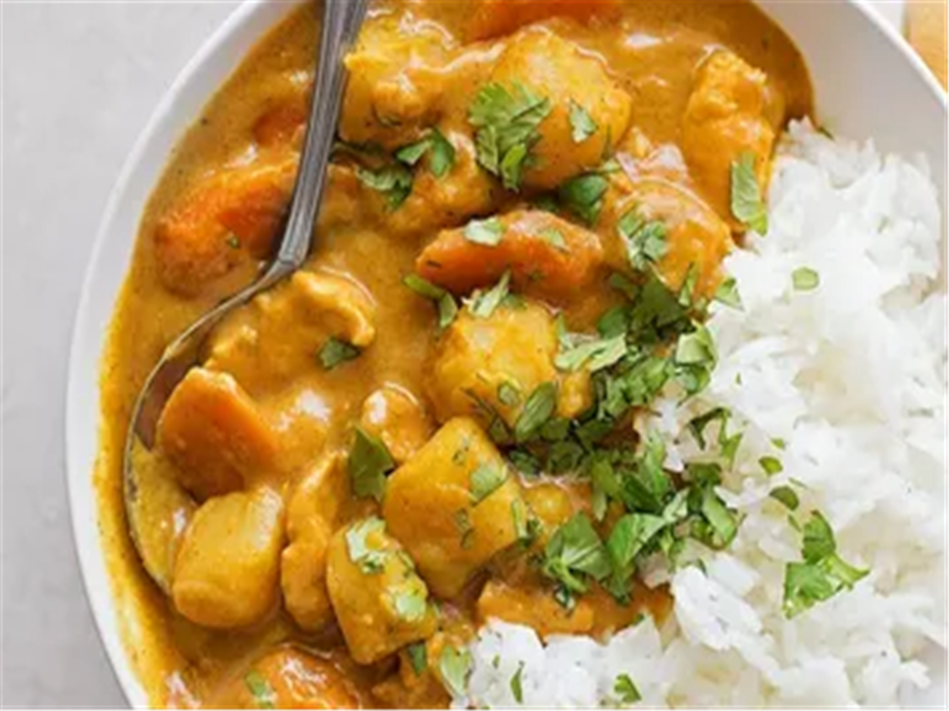 curry chicken: west indian style curry chicken served with white rice and vegetables