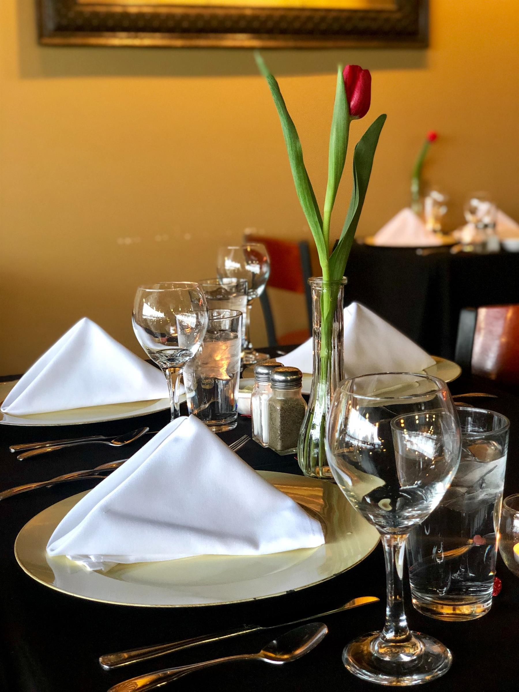 table set with plates, cloth napkins, silverware and glassware