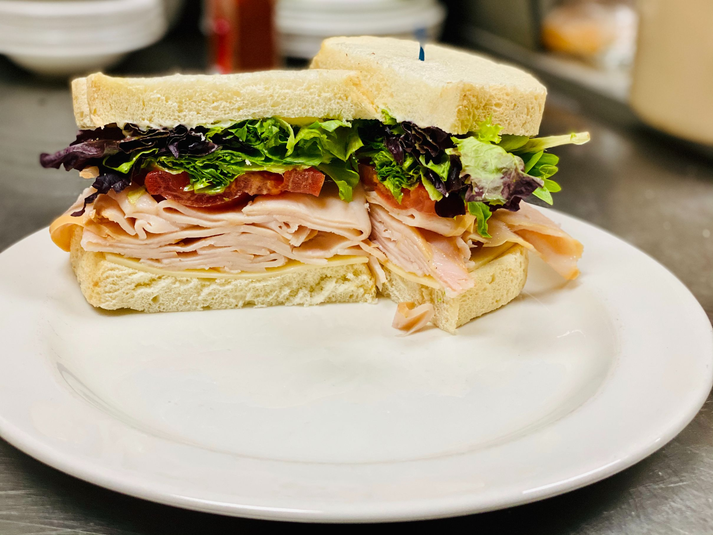 Turkey + Swiss Sandwich: Turkey, Swiss, red onion, spring mix, tomato, dijon mustard, and mayonnaise