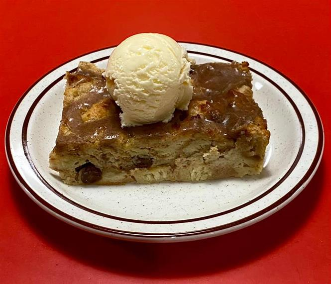 slice of bread pudding on a plate, topped with a scoop of vanilla ice cream