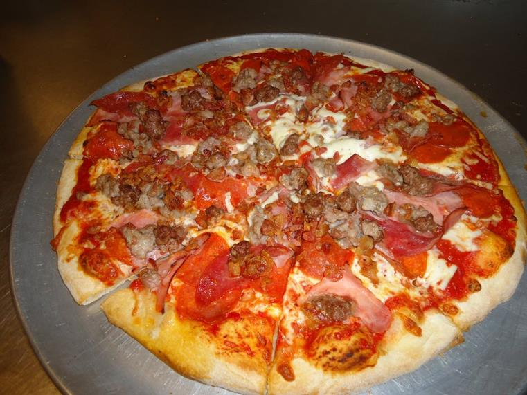 meat lovers pizza: pizza topped with pepperoni, ham, and sausage