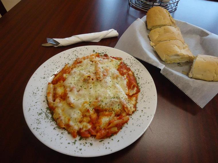 dish of baked ziti with melted cheese, basket of bread