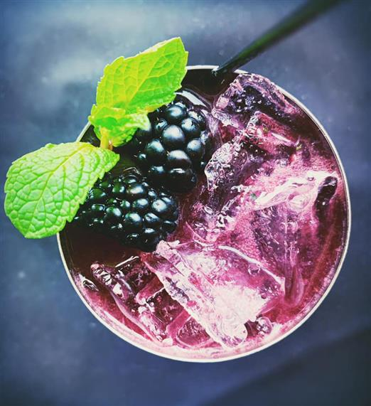 blackberry mule in a copper mug with blackberries and mint garnish