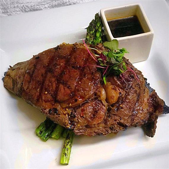 grilled steak with side of sauce and asparagus