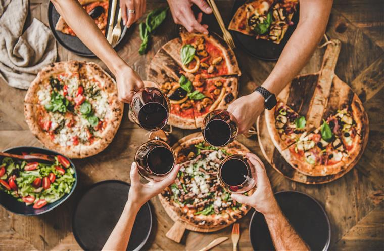 people toasting red wine over a table of pizzas