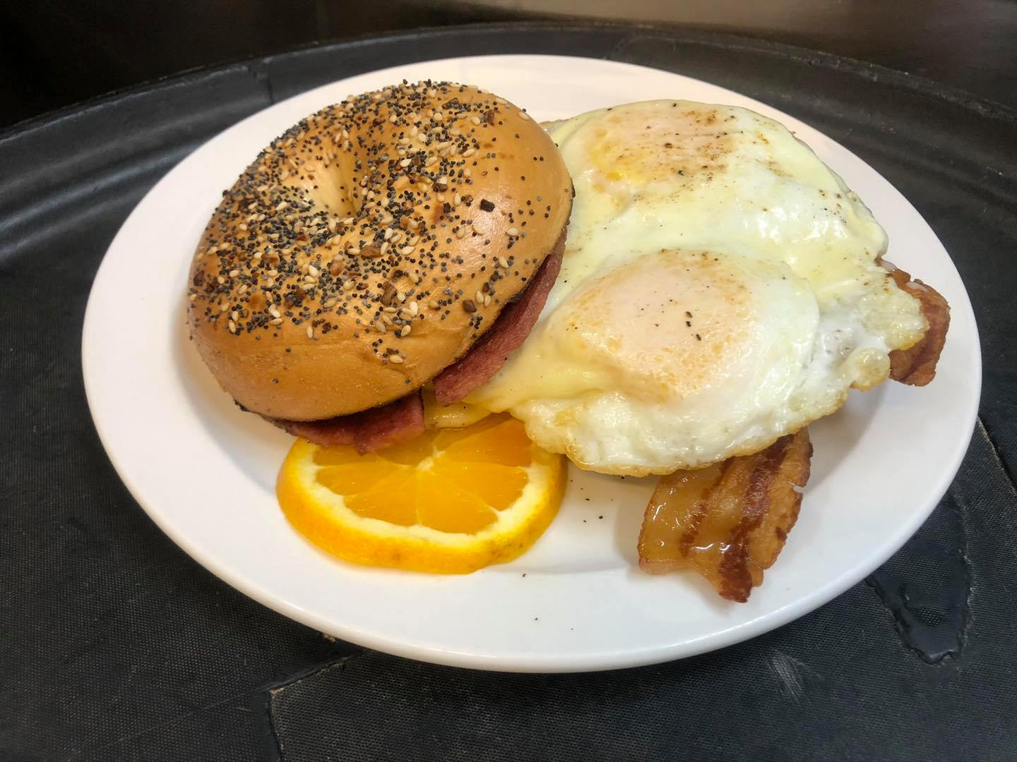 everything bagel with bacon and fried eggs with an orange wedge