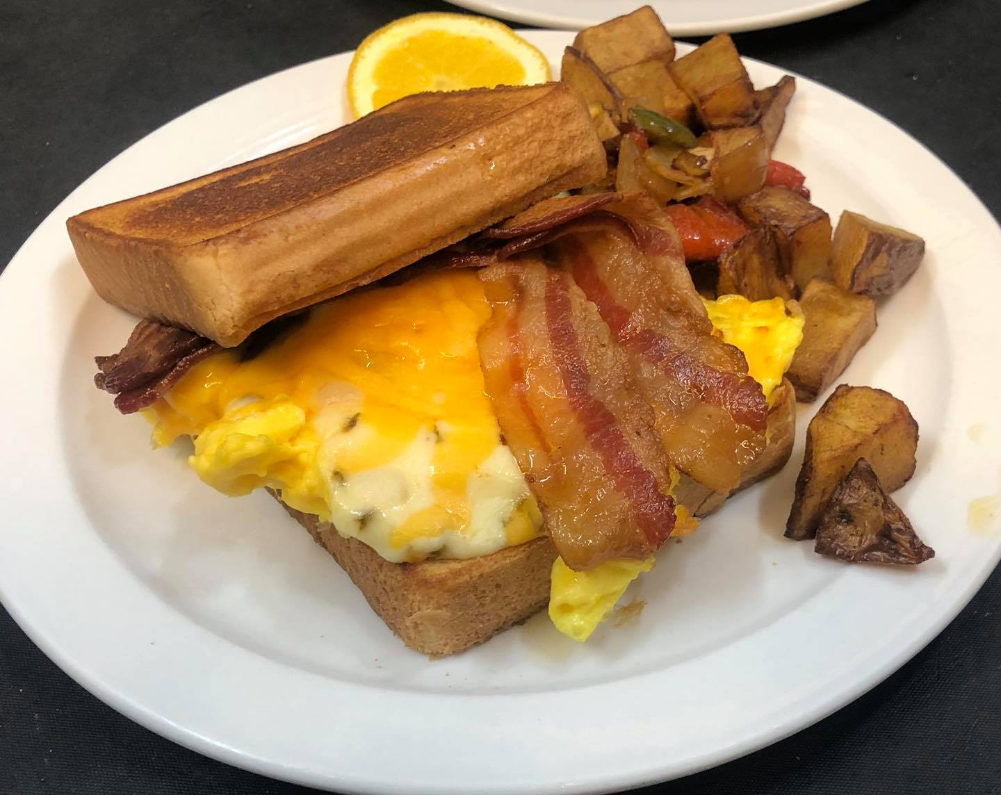 bacon, eggs, and cheese on toast with a side of home fries