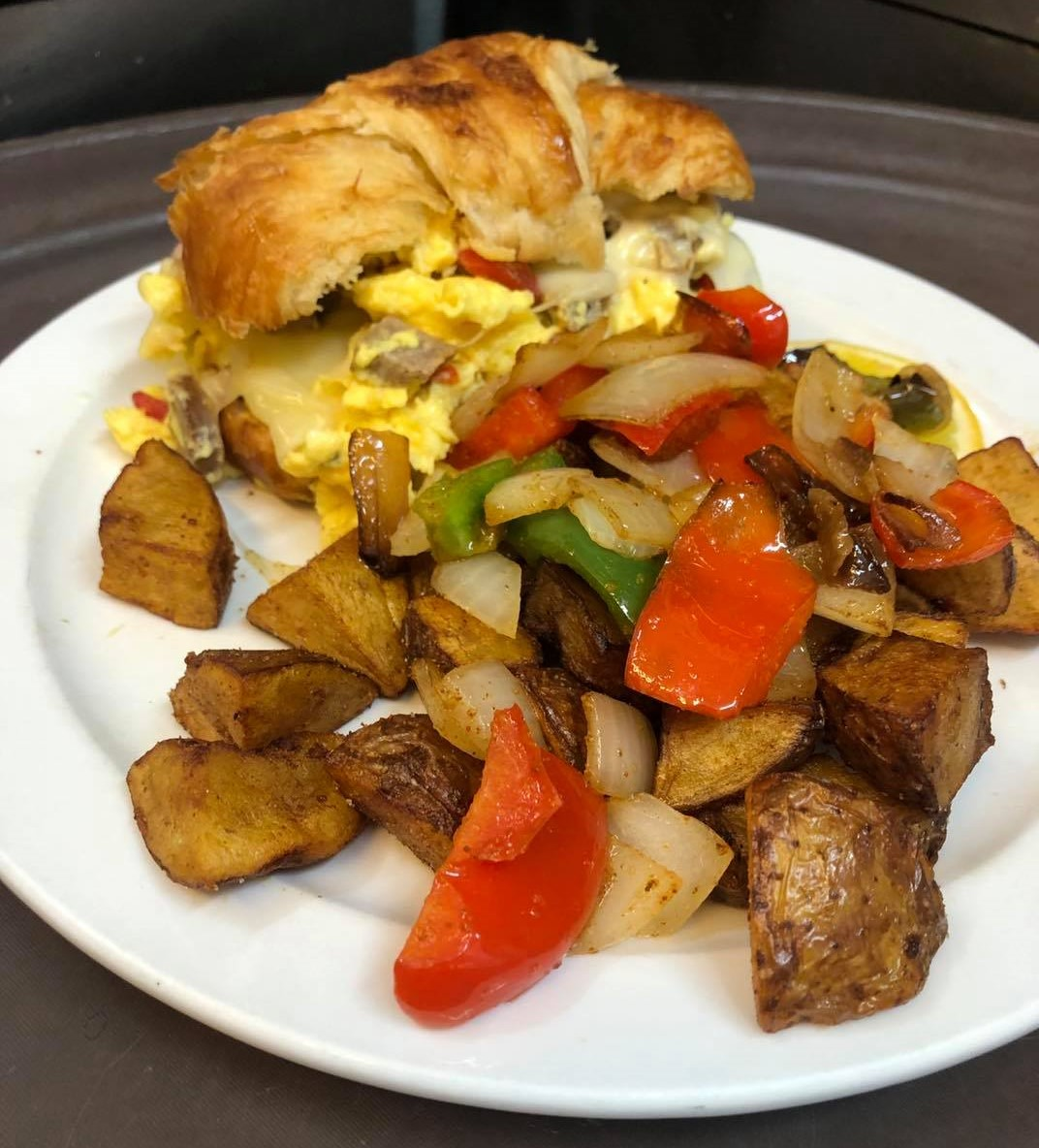 egg sandwich on a croissant with a side of home fries and roasted peppers