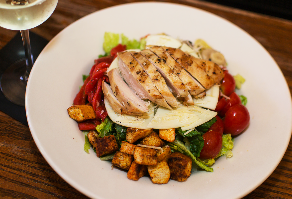 salad topped with grilled chicken, roasted peppers, tomatoes, and croutons