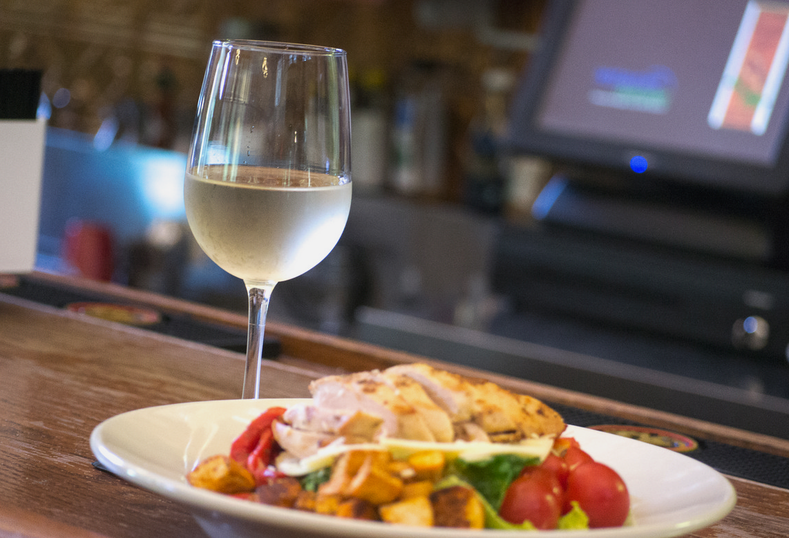 salad topped with grilled chicken, roasted peppers, tomatoes, and croutons with a glass of wine