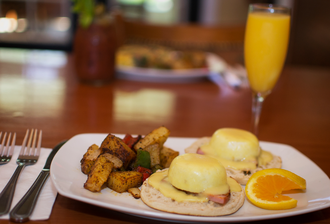eggs benedict with a side of home fries and an orange wedge with a mimosa