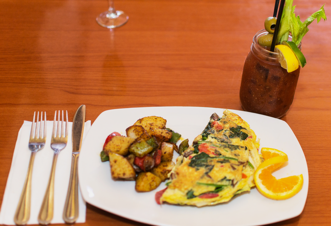 vegetable omelete with home fries and an orange wedge with a bloody mary