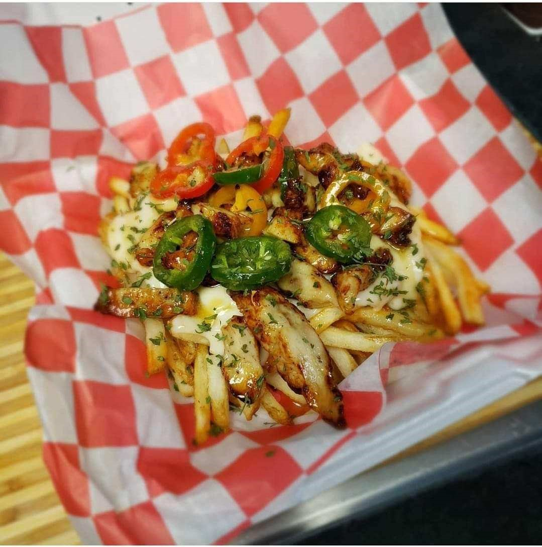 basket of chicken wings tossed in spicy sauce with peppers over fries