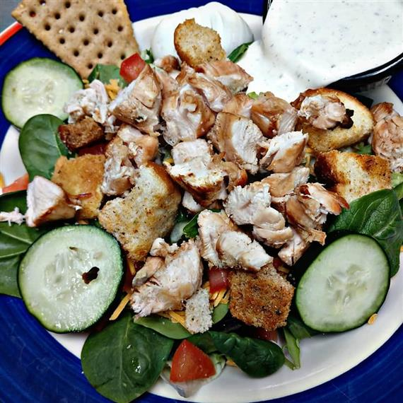 salad topped with chicken, croutons, tomatoes, cheese and cucumber