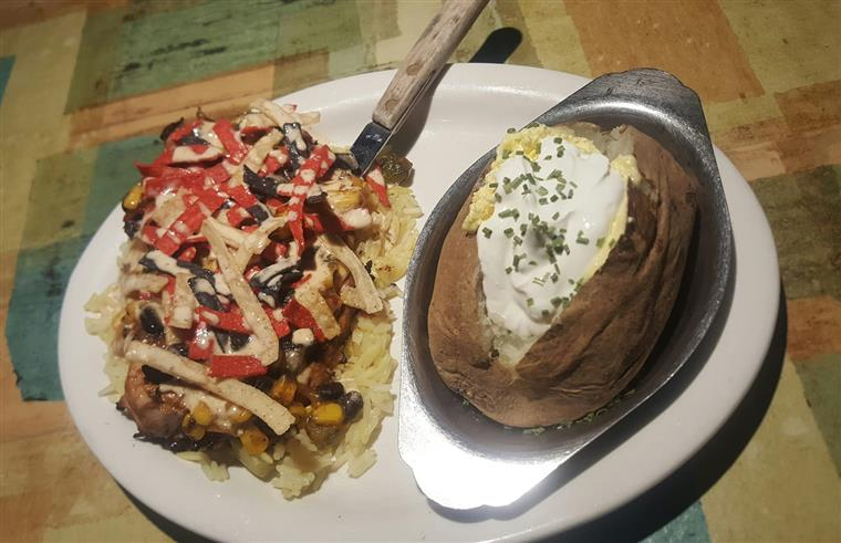 fiesta chicken on bed of rice topped with tortilla strips, baked potato with sour cream on the side