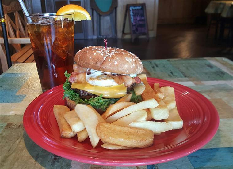 bacon cheeseburger topped with a fried egg, lettuce and tomato with steak cut french fries, glass of iced tea