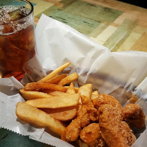 fried chicken strips, french fries and glass of iced tea