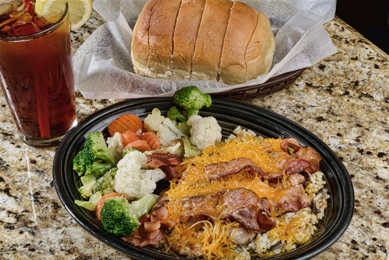 chicken topped with cheddar cheese and bacon, side of steamed vegetables. basket of bread and glass of iced tea