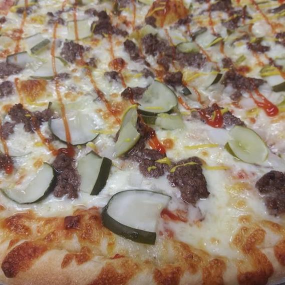 cheeseburger pizza with pickles, beef, cheese and mustard