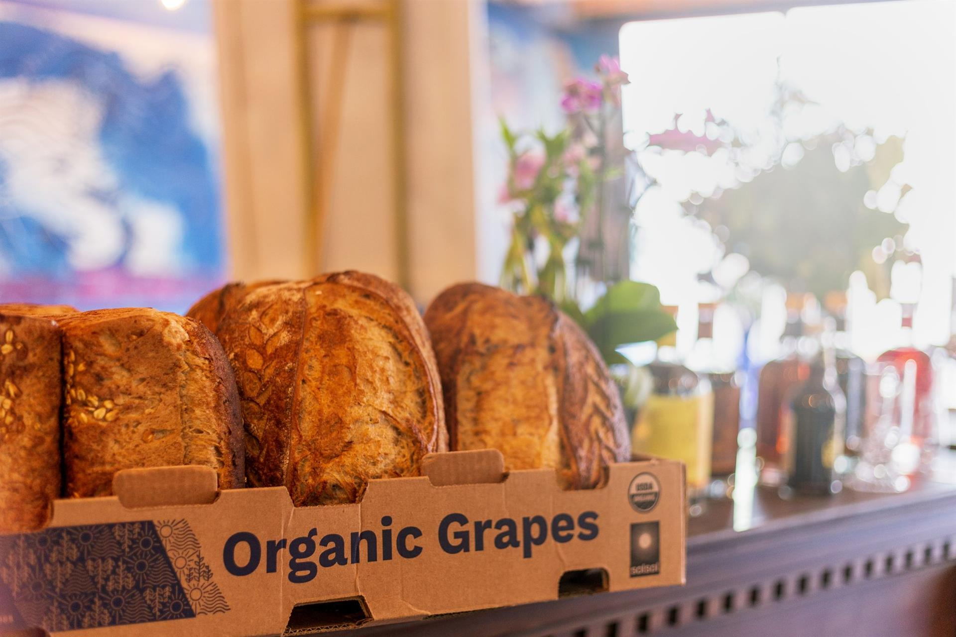 An Organic Grapes cardboard box full of loaved of bread