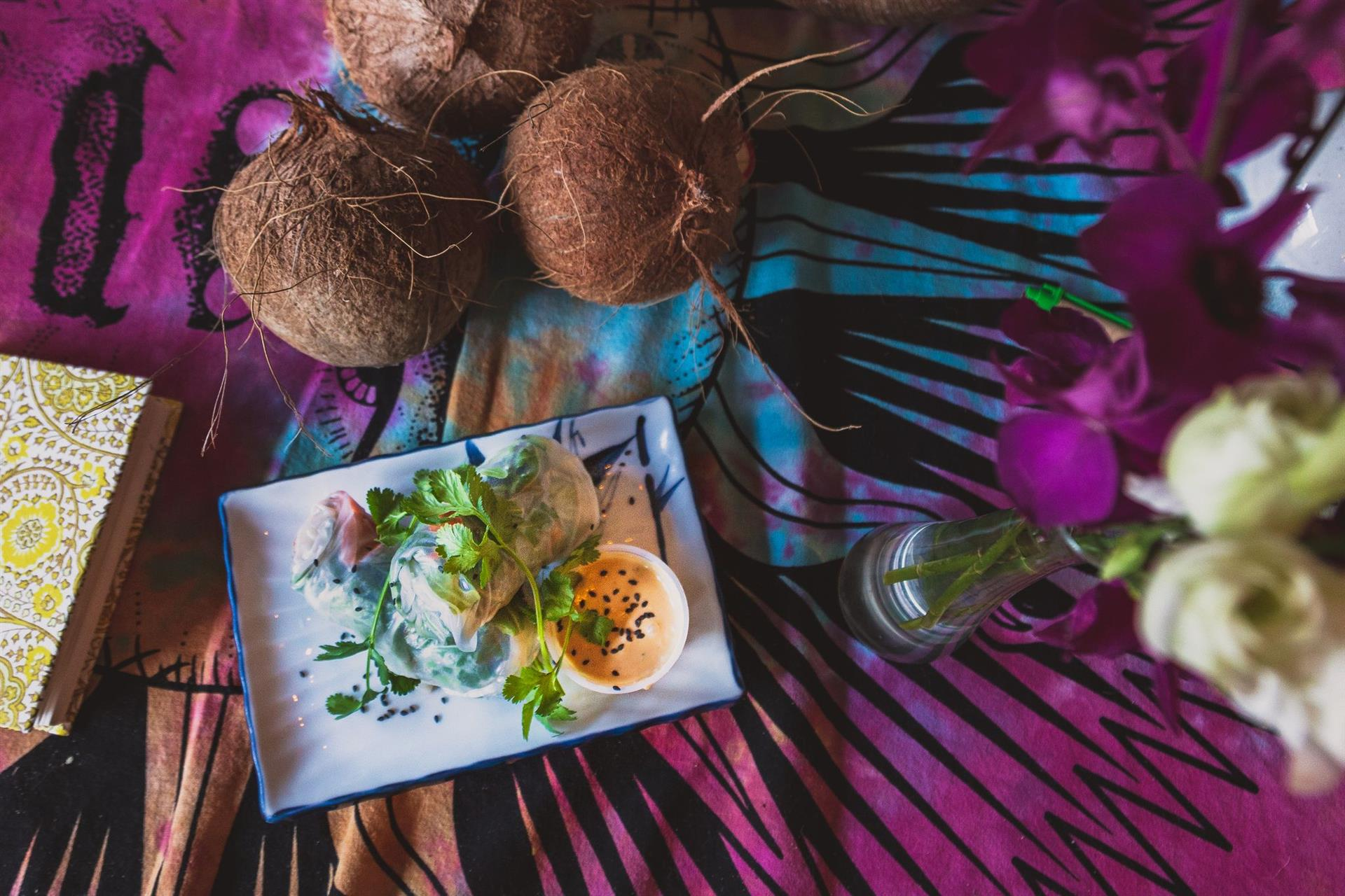 Small plate of food and coconuts on a bright tablecloth