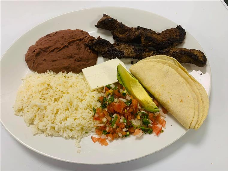 plate of meat, rice, beans and other sides