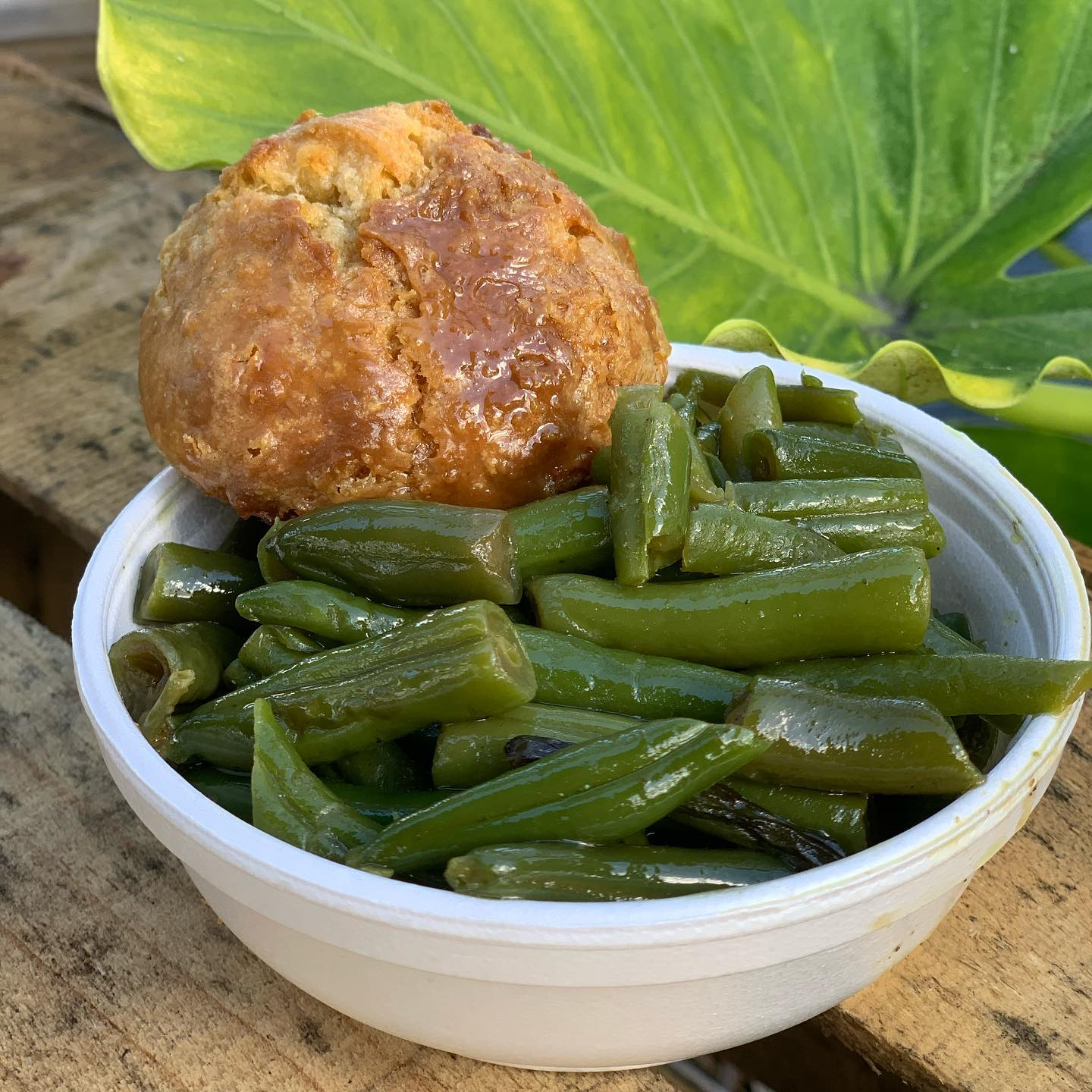 bowl of green beans with a biscuit