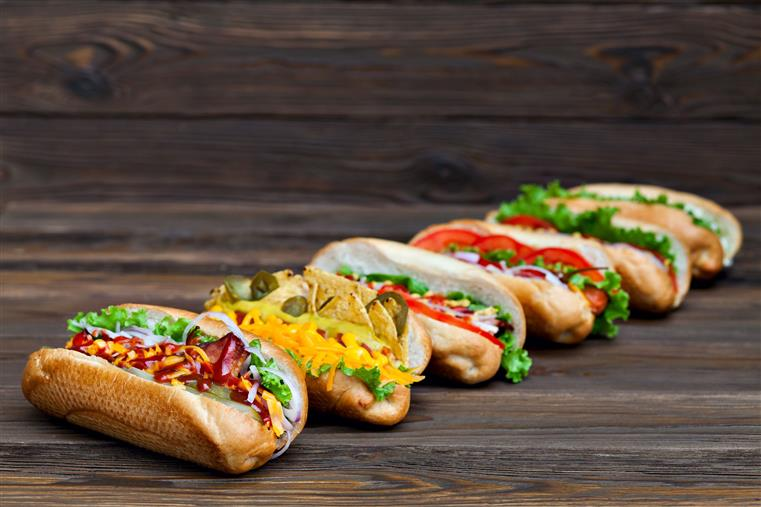 gourmet hot dogs topped with tomato, peppers, onion, lettuce, mustard, pickles, and jalapenos