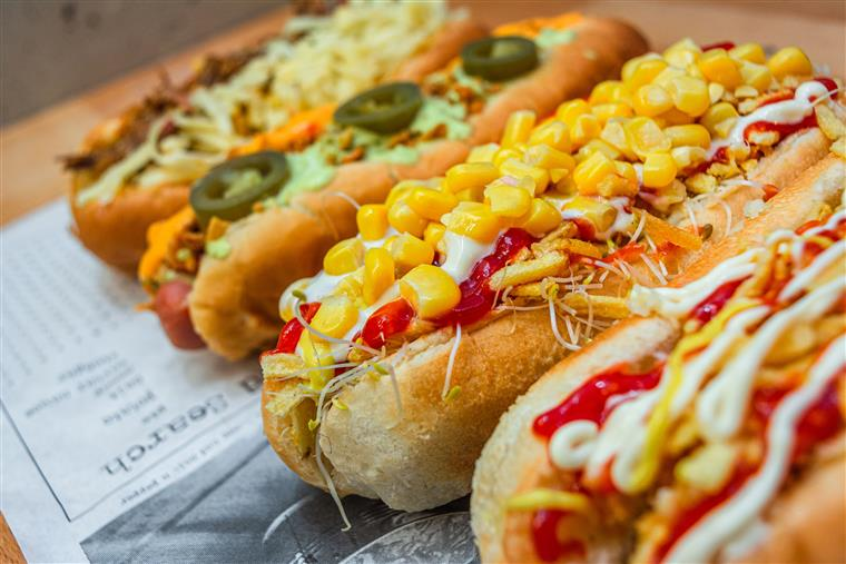 gourmet hot dogs topped with tomato, peppers, onion, lettuce, mustard, corn, pickles, and jalapenos