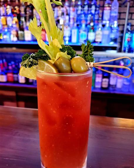 bloody mary with a stalk of celery and olives