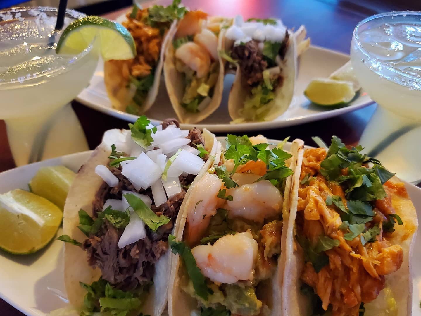 three tacos on a dish with a lime wedge