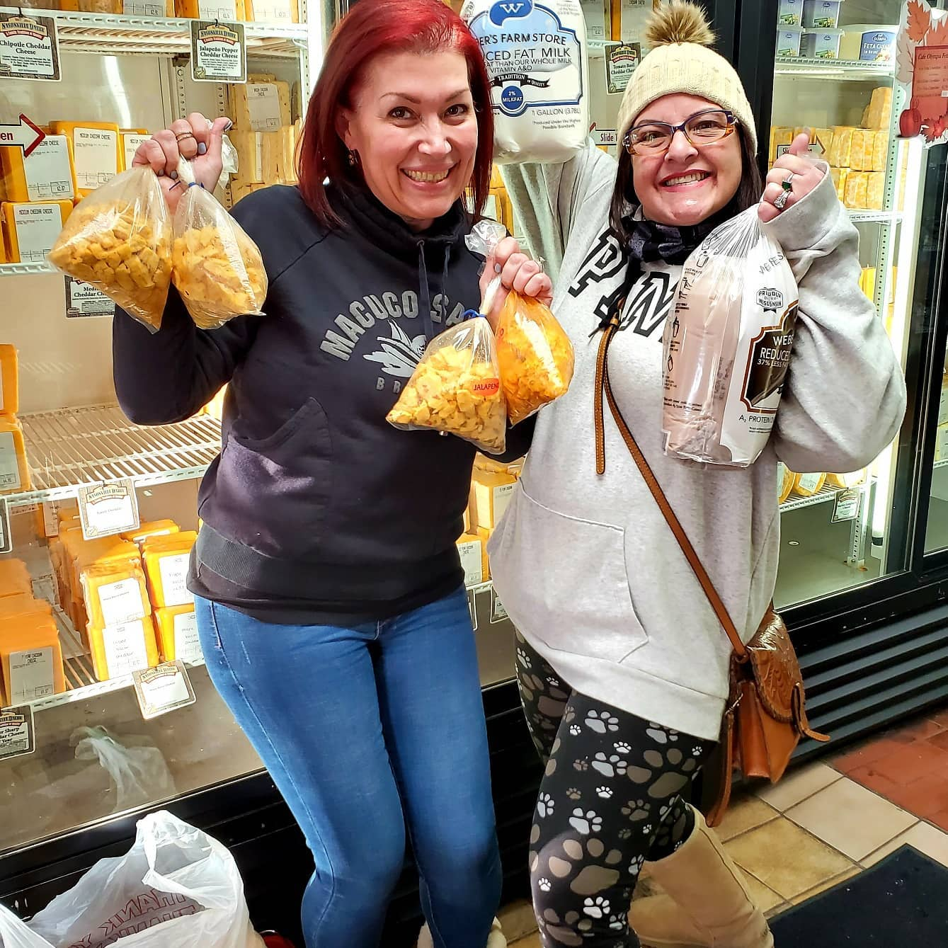 two women posing for a photo holding bags of cheese