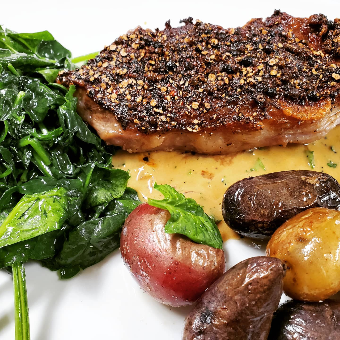 crusted salmon with a side of spinach and potatoes