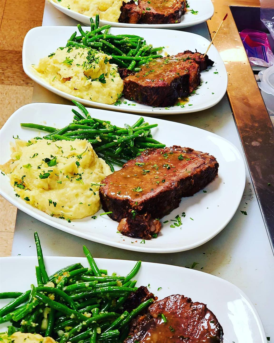 grilled steak with a side of mashed potatoes and green beans