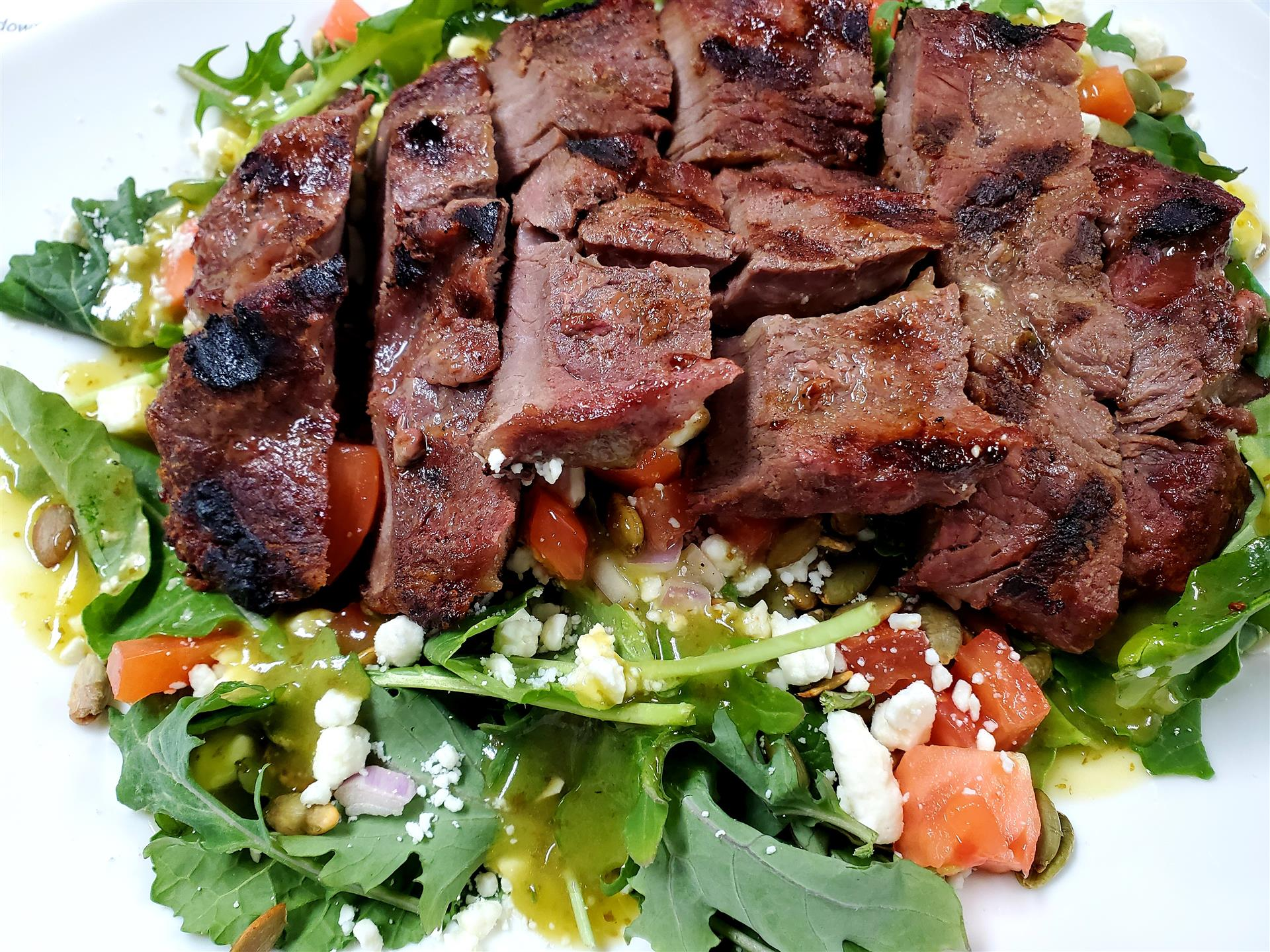 grilled steak salad with crumbled cheese and tomatoes