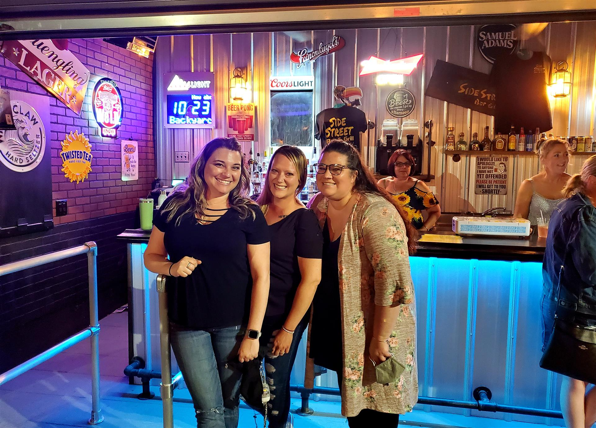 three women standing in front of the bar at side street