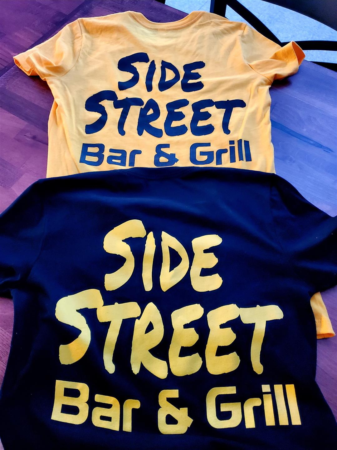 two t-shirts with side street bar and grill