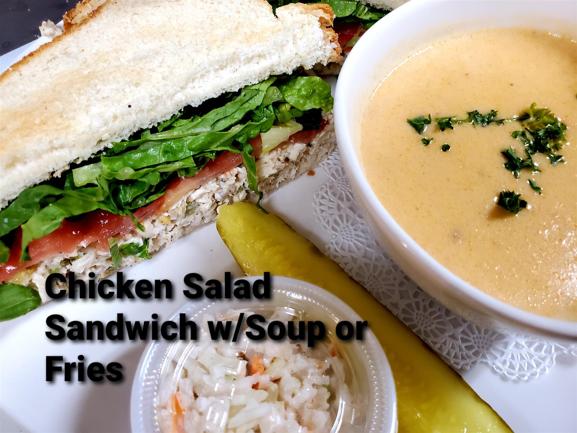 chicken salad sandwich with a bowl of soup, pickle, and a small side of cole slaw