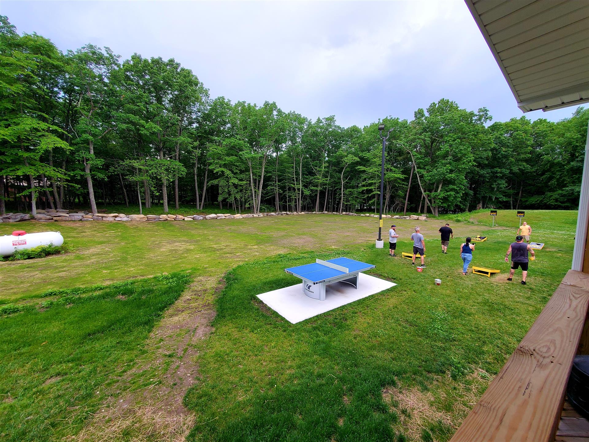 yard surrounded by trees with people playing cornhole