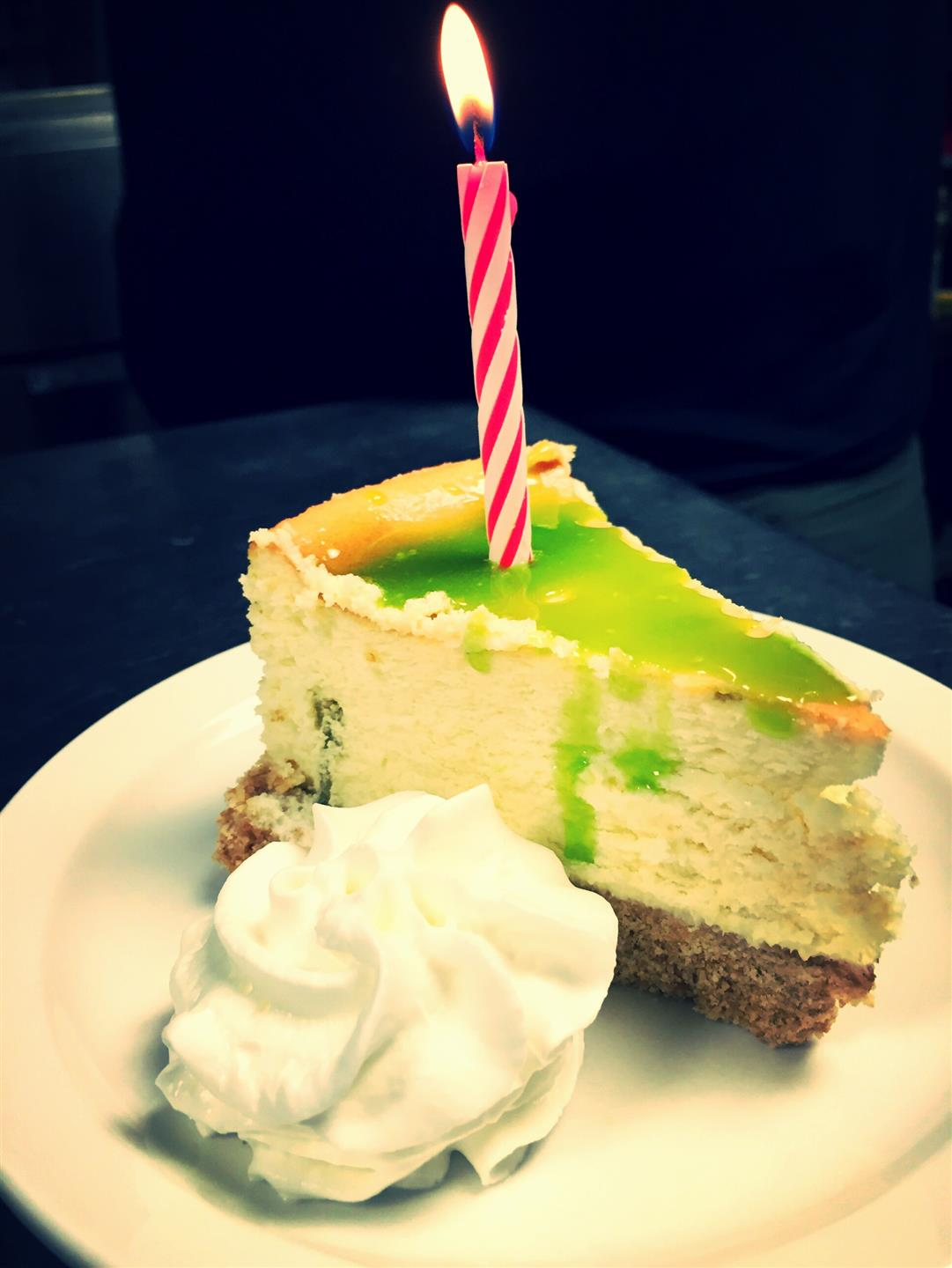 slice of cheesecake with a candle