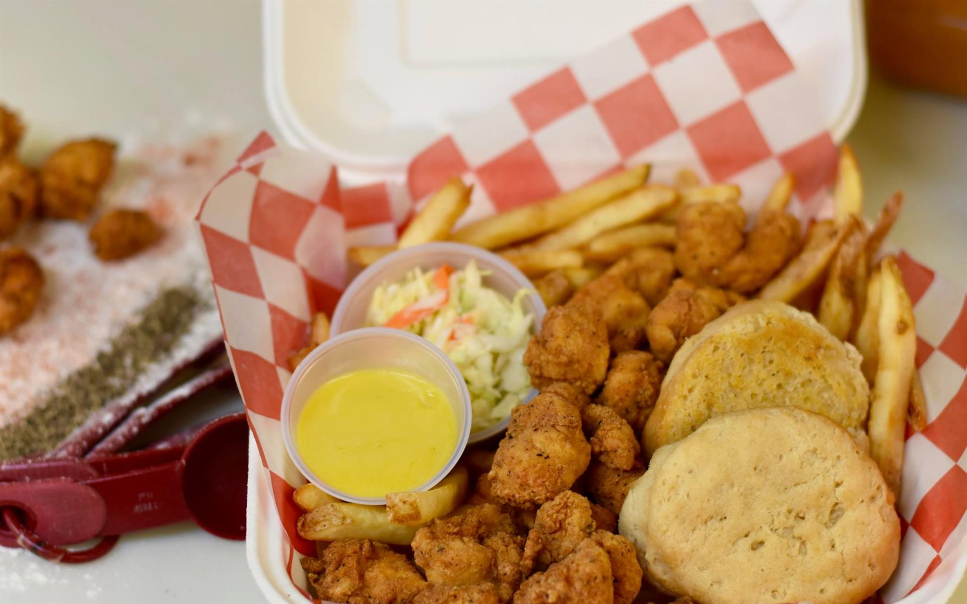 basket of popcorn chicken, fries, biscuits, with cups of coleslaw and honey mustard