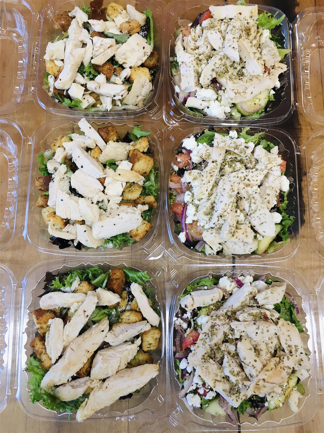 salad containers topped with chicken and croutons